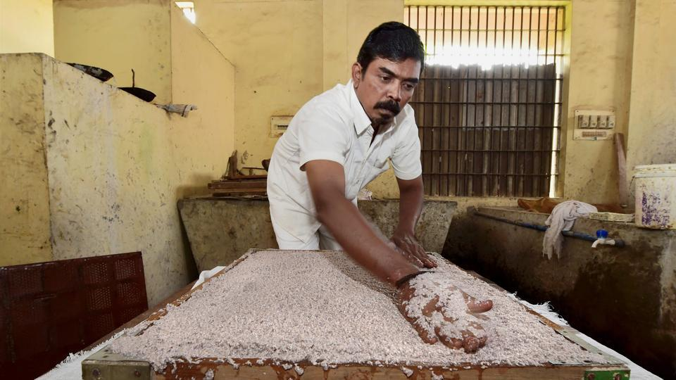 An inmate spreads demonetized currency pulp which eventually turns into hard pads, into a mould. The Reserve Bank of India offered 70 tons of shredded notes out of which about 1.5 tons has been used to make the holders so far. About 1,000 such holders are made daily at Puzhal prison. (R Senthil Kumar / PTI)