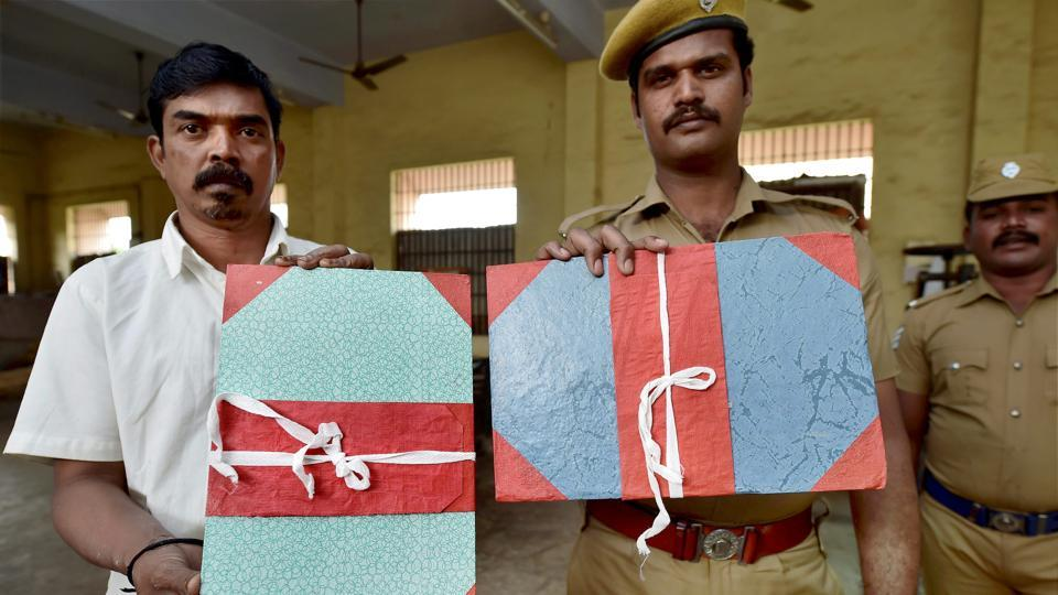 An inmate and a police personnel display finished file holders made by inmates at the jail. There is a proposal to upgrade the hand-made stationery unit into a semi-automated facility to enhance the productivity. Apart from stationery-making, the Central jails in the state also specialise in the production of shoe polish, soap and leather accessories. (R Senthil Kumar / PTI)
