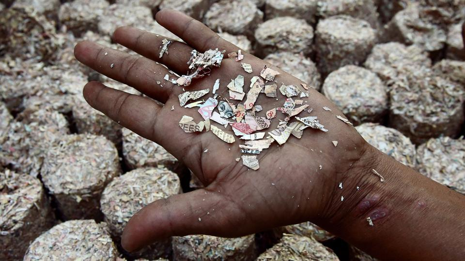 An inmate at the Puzhal Central Prison located in Chennai, Tamil Nadu shows shredded pieces of demonetised notes. Convicts serving life imprisonment terms at this prison are giving a fresh lease of life to demonetised currency, converting it into customised stationery for government use. (R Senthil Kumar / PTI)