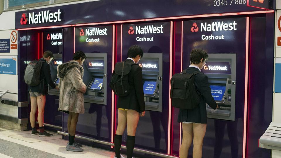 Men use cash machines at Liverpool Street station as they take part in No Trousers on the Tube day in London. Key to a successful No Pants Subway Ride is behaving as if participants do not know each other. (Dominic Lipinski / AP)