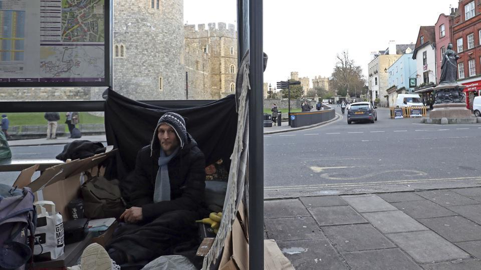 Stuart, no surname given, with his possessions in a bus stop near Windsor Castle, in background, in Windsor, England. A political storm is brewing ahead of Prince Harry and Meghan Markle's May 19 wedding over whether to crack down on homeless people and beggars in the well-to-do English town of Windsor.