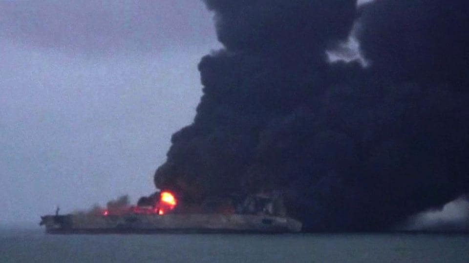 Smoke and flames coming from a burning oil tanker at sea off the coast of eastern China.