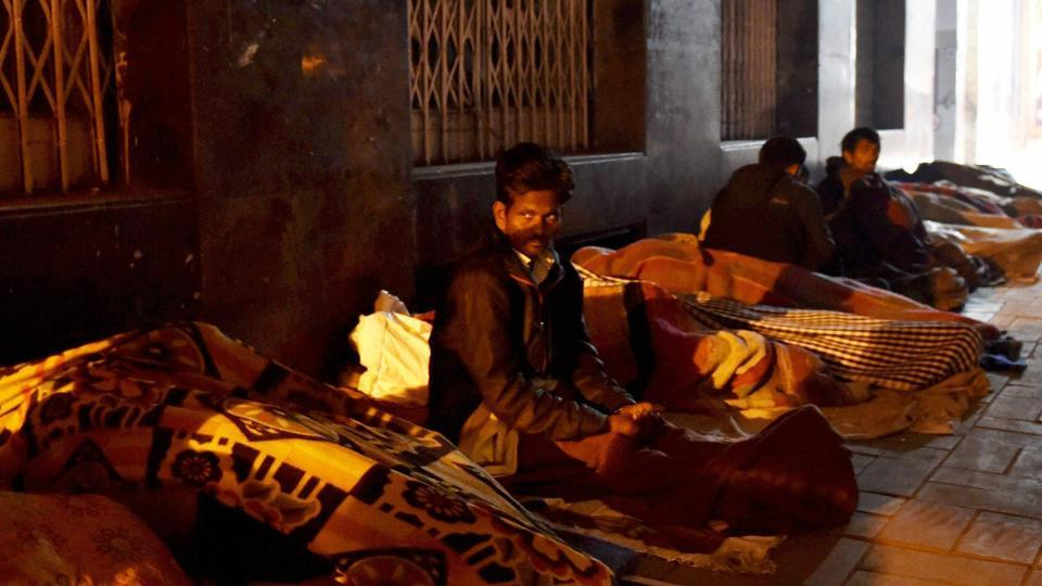 Homeless people sleep on a roadside in a cold evening in New Delhi on January 4, 2018.