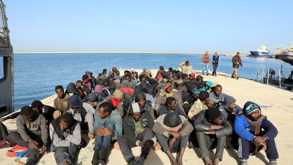 Migrants sit at a naval base after they were rescued by Libyan coast guards, at a naval base in Tripoli, Libya.