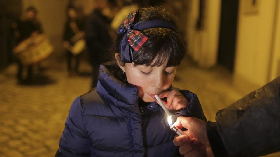An adult helps a young girl light a cigarette as a band plays in the background in the village of Vale de Salgueiro, Portugal during the local Kings' Feast on January 05, 2018. The village's Epiphany celebrations, called Kings' Feast, feature a tradition that each year causes an outcry among outsiders: parents encourage their children, some as young as 5, to smoke cigarettes. (Armando Franca / AP)