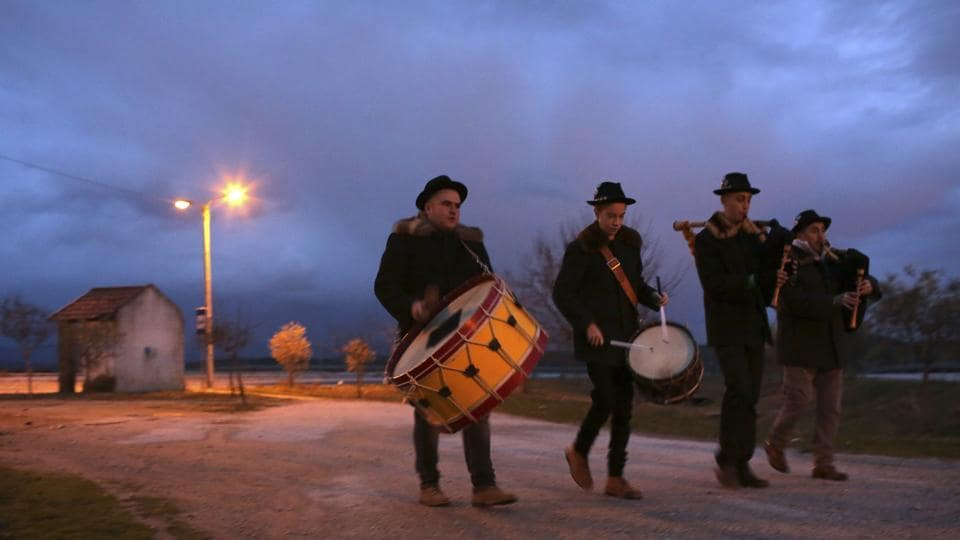 A band with bagpipes enters the village of Vale de Salgueiro, opening the local Kings' Feast as night falls. The two-day celebrations began last Friday and ended Saturday with a Mass. (Armando Franca / AP)