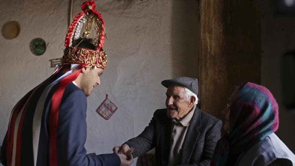 Jose David Mateus (C), 100, and his wife Adilia, 86, hand their contribution to this year's 'king', Alexandre Taveira (L), for the Kings' Feast. The annual 'king' is responsible for organizing the village's Epiphany celebrations and goes about distributing plentiful wine and snacks. (Armando Franca / AP)