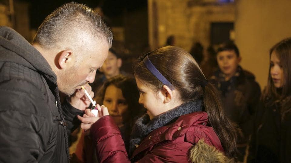 Luisa Ines, 10, gets her father Carlos Cadavez, a non-smoker, to help her light a cigarette. The legal age to purchase tobacco in Portugal is 18, but nothing prohibits parents from giving kids cigarettes and Portuguese authorities don't intervene to stop the practice. (Armando Franca / AP)