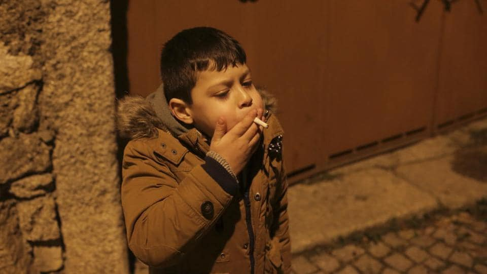 "A young boy smokes in the street in the village of Vale de Salgueiro. Ribeirinha also believes the seclusion of the village has helped keep the tradition alive. He said that the surrounding Tras os Montes region ""has always been the furthest from Lisbon, the most 'forgotten one.'"" (Armando Franca / AP)"