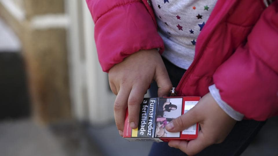 Natasha, 8, holds a packet of cigarettes during the Kings' Feast Saturday. Portugal, like many other European countries, has generally taken steps to reduce smoking, including a partial ban on smoking indoors. (Armando Franca / AP)