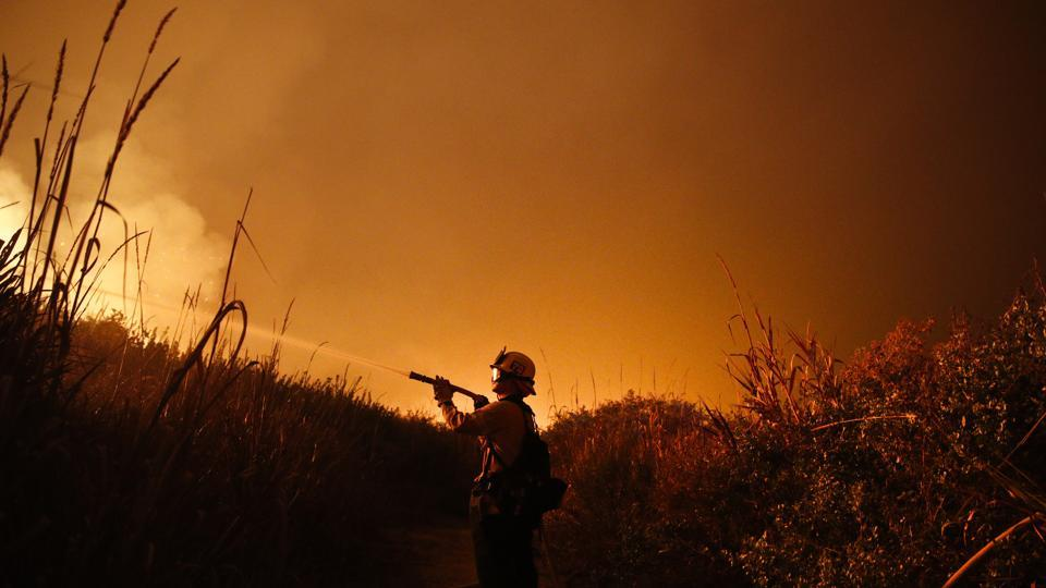 In this Dec 7, 2017 photo, a firefighter battles a wildfire as it burns along a hillside toward homes in La Conchita, California. With three strong hurricanes, wildfires, hail, flooding, tornadoes and drought, supersized weather disasters tallied a record high bill for America in 2017: $306 billion.