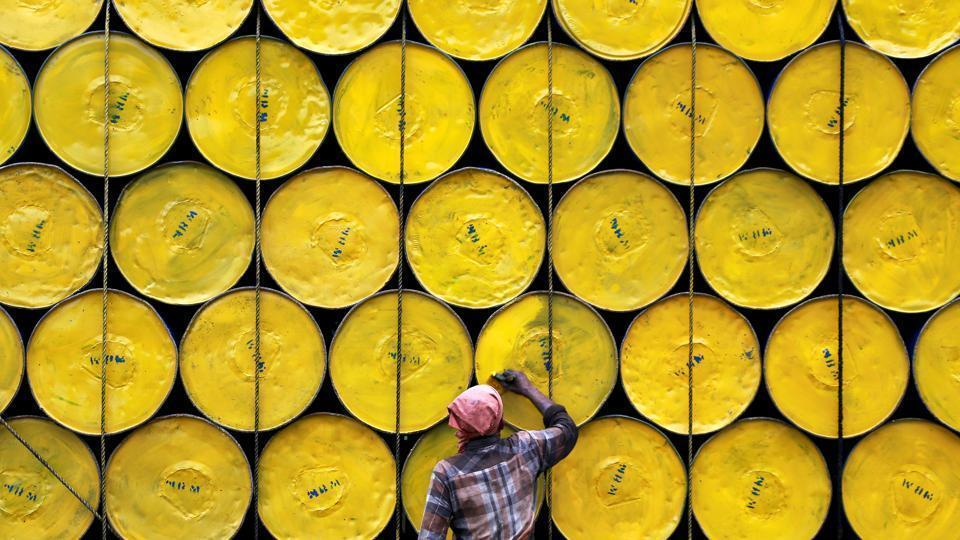 A worker paints empty barrels loaded onto a truck at a roadside in Kochi, India June 29, 2017.