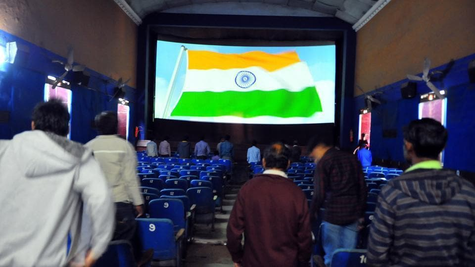People stand up for the national anthem before the start of a movie at a theatre  in Indore.