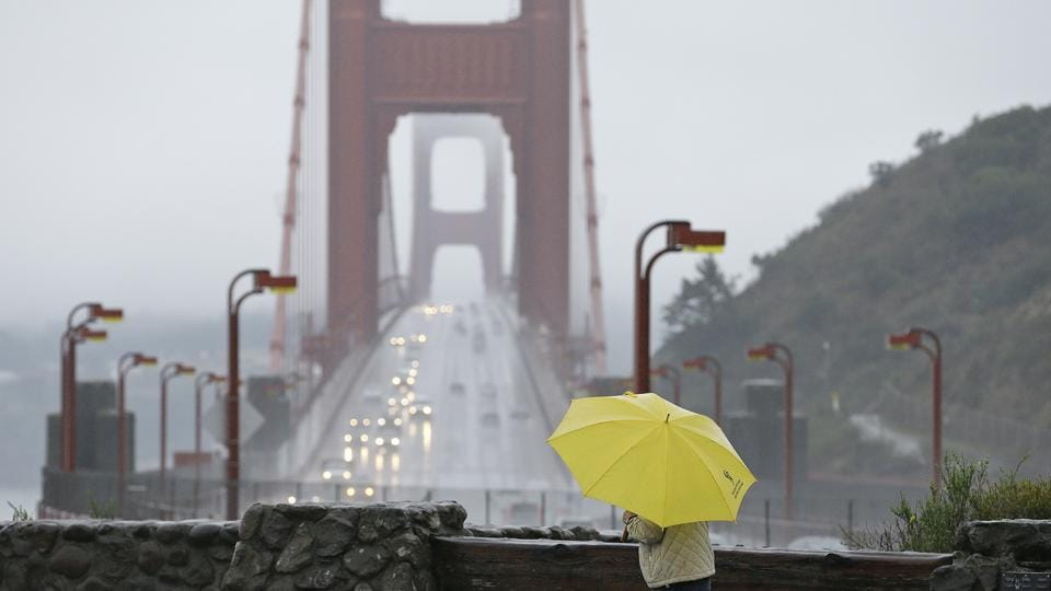 A woman walks in the rain at a vista point with the Golden Gate Bridge in the background on Monday.