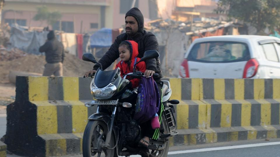 A child contorts her face in the cold wind as her father takes her to school on Monday, first day of the extended winter break.