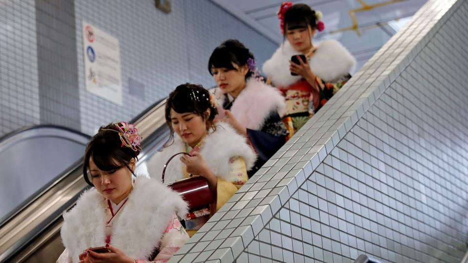 Japanese women heading to the day's celebrations ride an escalator at a subway station. Coming of Age Day includes those who turned 20 the previous year or will do so before March 31. The elaborate clothing and made-up participants draw spectators and news crews every year. (Kim Kyung-Hoon / REUTERS)