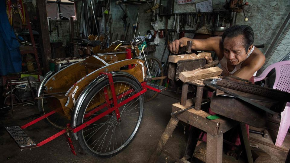 Surrounded by a trove of tools and spare parts, trishaw maker Aye Zaw works on his latest model, readying it for the clogged roads of Myanmar's biggest city. Despite marked changes to Yangon's streets, the 46-year-old revels in defying time with this traditional form of transport. (Roberto Schmidt / AFP)