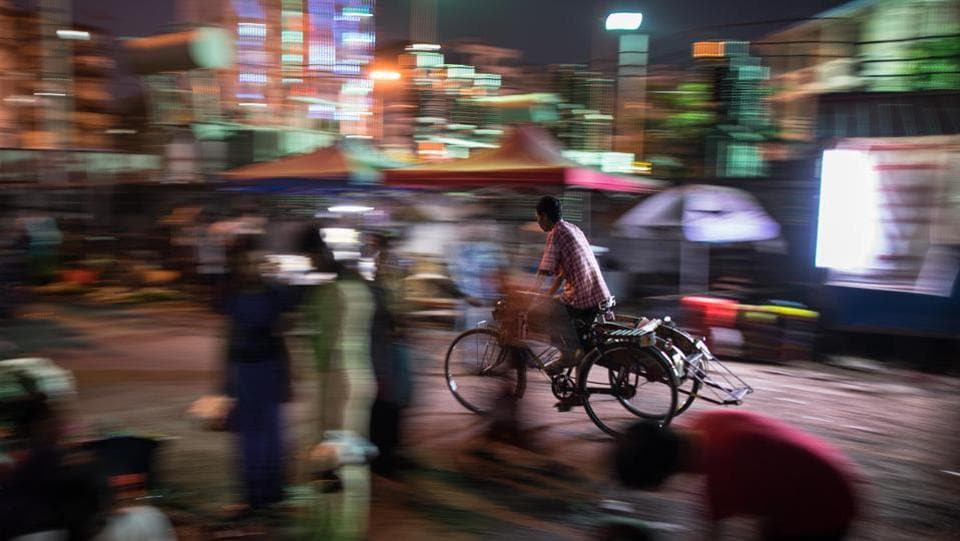 A trishaw driver cycles past street vendors in a market in the early evening hours. Myanmar has seen an explosion in vehicle numbers after a military-backed government eased car imports. The country has since tried to improve congestion by overhauling the bus system, building flyovers, upgrading a circular railway line, and most recently, introducing water taxis. (Roberto Schmidt / AFP)