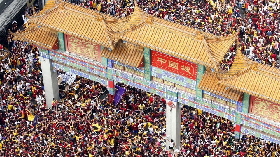 The raucous procession of the image of the Black Nazarene enters the arch landmark of Manila's Chinatown during its celebration of its feast day on January 9, 2018, in Manila, Philippines.