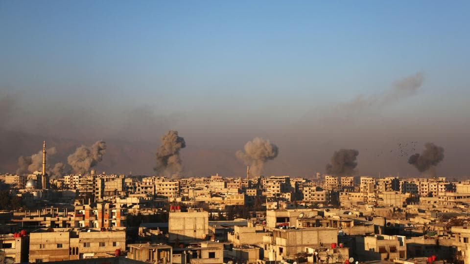 Smoke rises from buildings following air strikes on the rebel-held besieged town of Arbin, in the eastern Ghouta region on the outskirts of the capital Damascus on January 8, 2018.