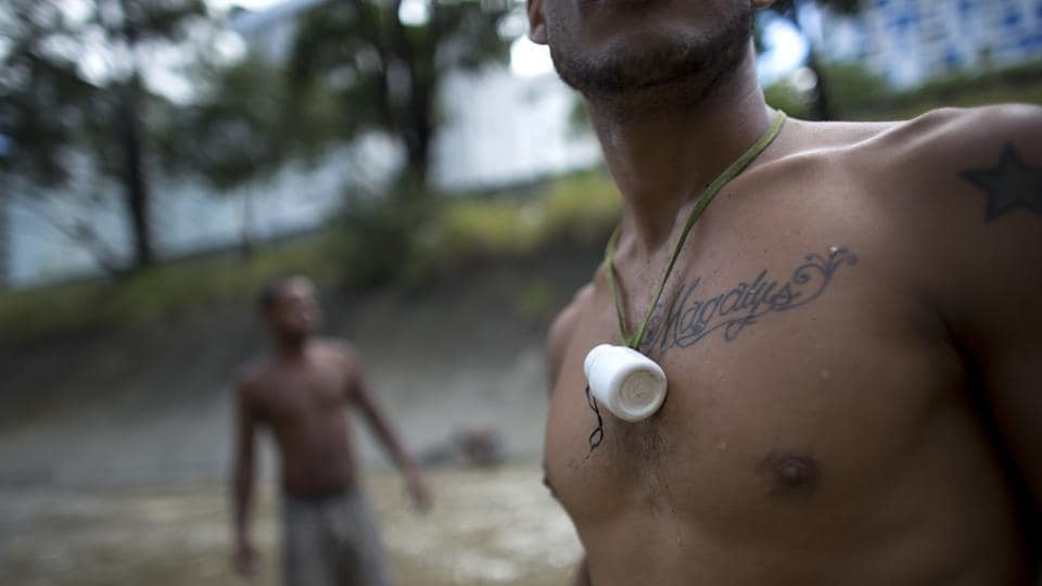 A medicine bottle hangs from a scavenger's neck, where he keeps the small pieces of gold and other finds from the water. The day's haul -- a keychain and an old coin -- is taken to the Bolivar Plaza, where vendors offer cash for gold. (Ariana Cubillos / AP)