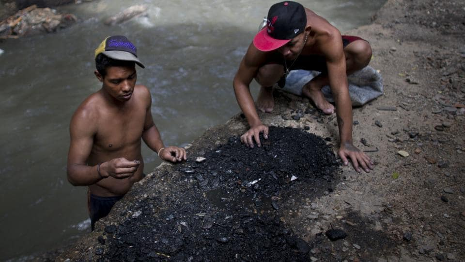 Images of Venezuelans eating from garbage piles have come to symbolize the deepening economic crisis. Less visible are the young men who comb these waters to feed families. At times playing, shirtless and laughing in groups, the sun reflects off their backs as they scoop up rocks and toss them aside in waters that are also drains for sewage and industrial waste. (Ariana Cubillos / AP)