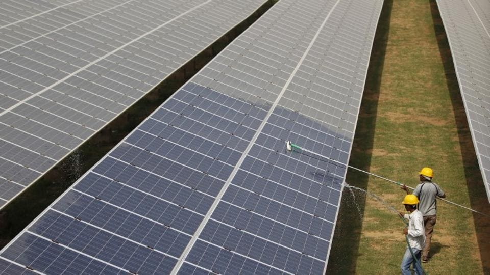 Workers clean photovoltaic panels inside a solar power plant, Gujarat.