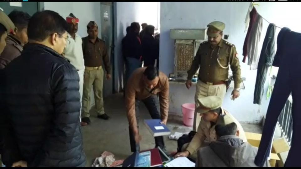 Police and officials searching through items in Kashmiri scholar Mannan Bashir Wani's hostel room in the varsity campus.