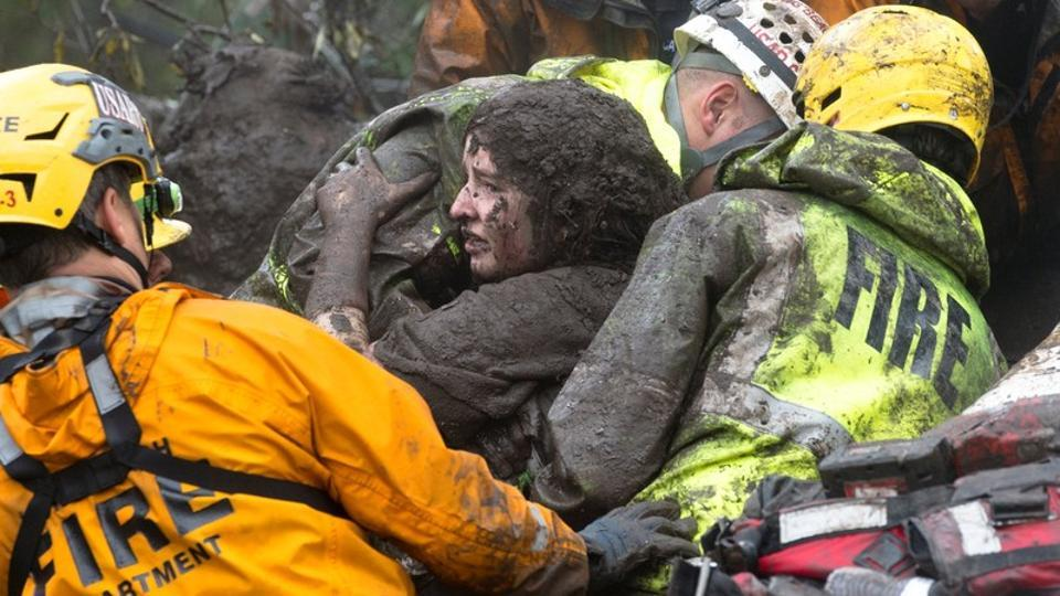 Emergency personnel carry a woman rescued from a collapsed house after a mudslide in Montecito. Mudslides, boulders and tons of debris killed at least 13 people on Tuesday in communities along California's scenic coastline ravaged by a series of intense wildfires that burned off protective vegetation last month. (Kenneth Song / Santa Barbara News-Press / REUTERS)