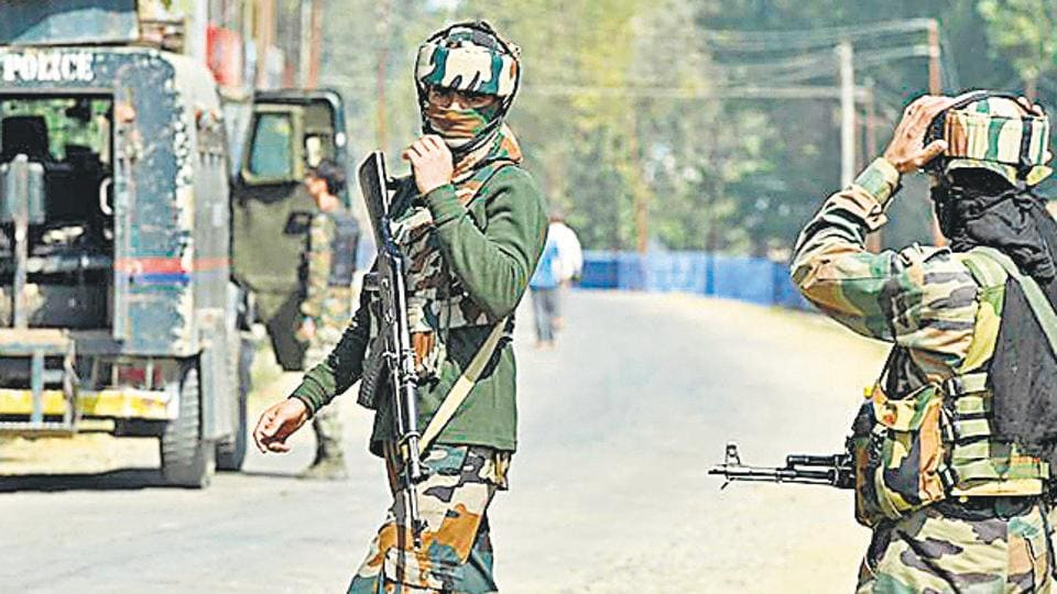 Security forces stand guard at village in restive  Kashmir valley.