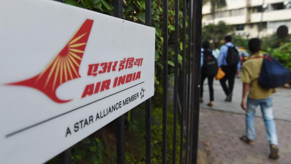 Pedestrians walk past a sign of state carrier Air India outside its headquarters in Mumbai. The state carrier will be opened up for investment by foreign companies, the government decided on January 10.
