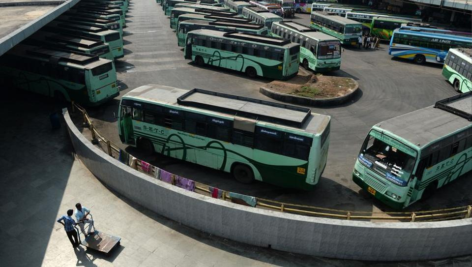 Travellers stand next to buses parked at a depot during a transport strike in Chennai on January 5.