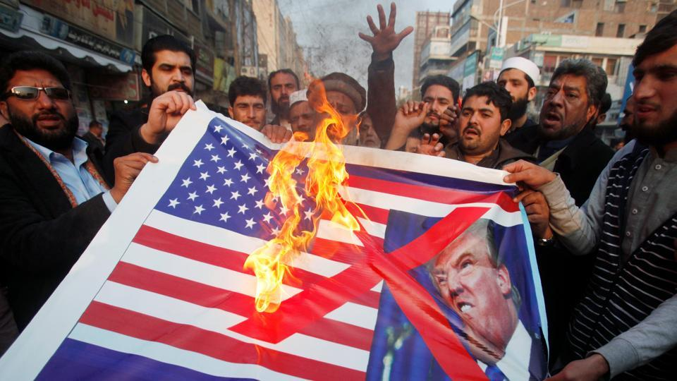 People burn a sign depicting a US flag and a picture of US President Donald Trump as they take part in an anti-America rally in Peshawar, on January 5, 2018.