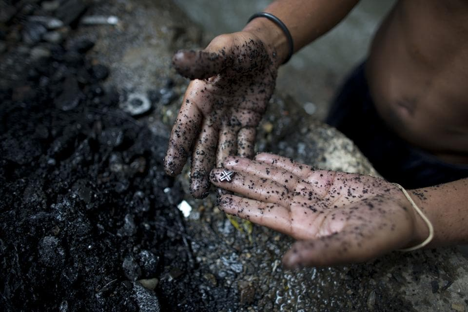 A scavenger shows his haul from the Guaire river bottom, where men search for bits of precious metal to cash in for food. Nearly two decades of socialist rule have seen Venezuela's food and oil production plummet amid poor management of state resources, and a drop in world crude prices has driven many to desperate means for livelihoods. (Ariana Cubillos / AP)