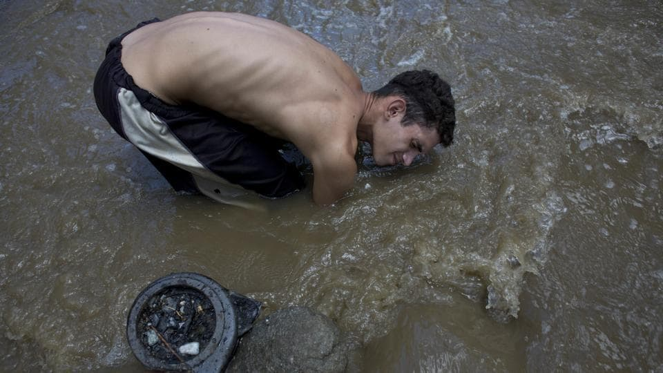David Garcia, 19, keeps his head barely above water raking the bottom of the Guaire River in search of valuables to sell in Caracas. Still in his first week working in the toxic, drain fed waters he said that his family was unaware this was how he was trying to put food on the table. He is one among many in crisis-hit Venezuela driven to scavenging in this polluted river. (Ariana Cubillos / AP)