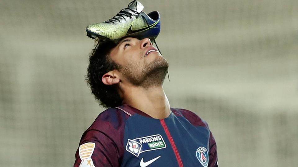 Paris Saint-Germain's Neymar celebrates scoring their first goal from the penalty spot with his football boot on his head.