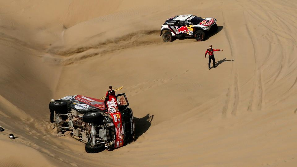 Sebastien Loeb of France and co-driver Daniel Elena of Monaco drive past  the crashed car of Janus Van Kasteren and Wouter De Graaff of the Netherlands during stage 5 of the Dakar Rally. Later, Loeb pulled out of the rally too after Elena injured his back in a crash.