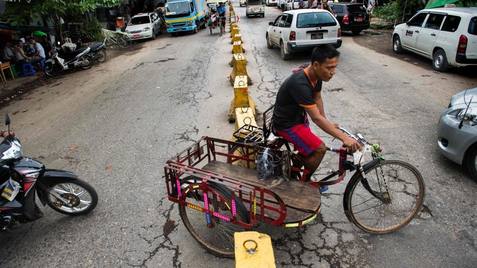 A trishaw driver makes a turn on a street in Yangon. Some 25,000 licensed drivers of three-wheeled trishaws pedal away, undeterred by the rapid transformation of the city's streets from sedate thoroughfares to car-choked arteries in just a few years after economic reforms were launched in 2011 opening the country after years of isolation. (Roberto Schmidt / AFP)