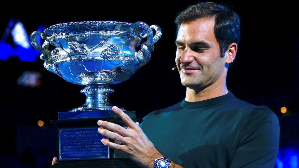 Roger Federer holds the men's singles trophy as he participates in the official draw ceremony ahead of the Australian Open tennis tournament.
