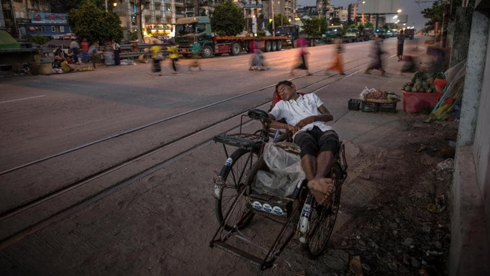 "A cycle trishaw driver naps while waiting for customers  in Yangon. Sixty-year-old Aung Ba is one of the city's 25,000 such drivers, earning about 10,000 kyat (Rs. 480) each day. ""It wouldn't be good to drive a car. But riding a trishaw, I can find my way through as I want,"" he said sitting beside his vehicle. (Roberto Schmidt / AFP)"