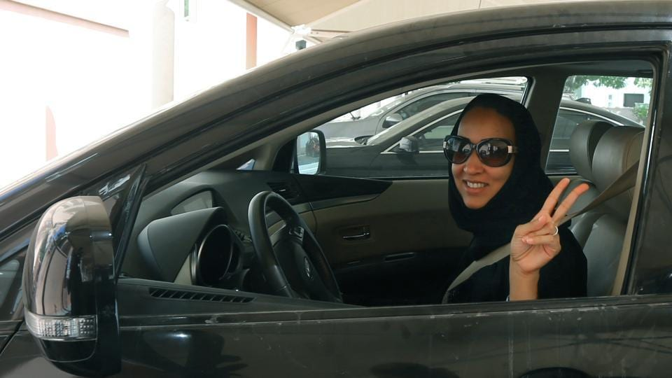 Saudi activist Manal Al Sharif, who now lives in Dubai, flashes the sign for victory as she drives her car in the Gulf Emirate city on October 22, 2013.