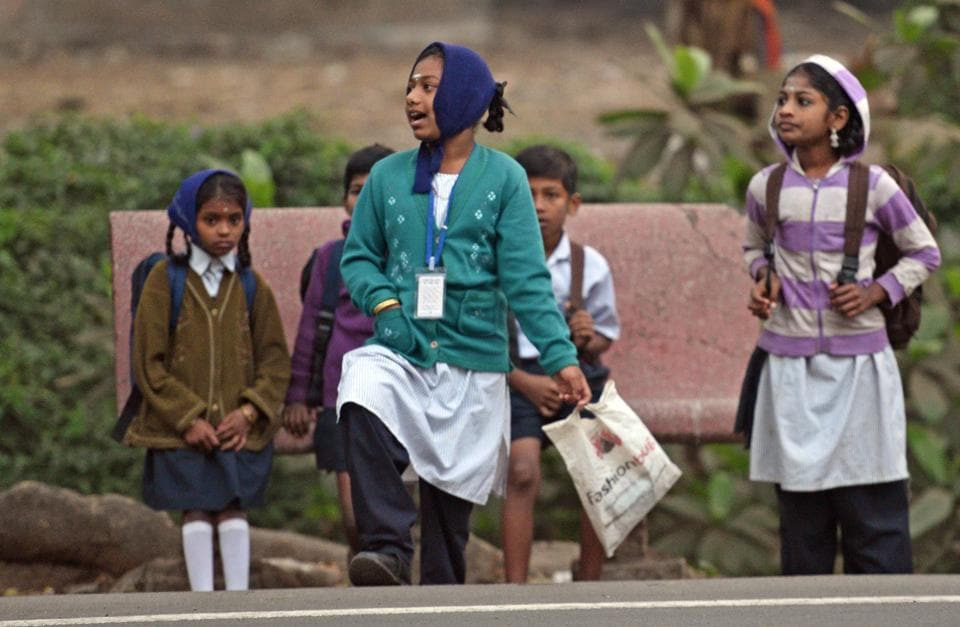 Children wait for their school bus in sweaters early morning in Mumbai.