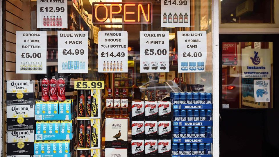 A liquor store displaying bottles and cans with price tags in the window.