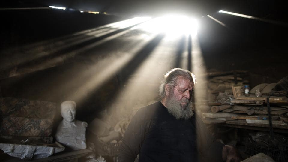 Rays of sunlight shine on Haralambos Goumas as he works in his workshop. His pieces are a rare survival of a vanishing art in recession-plagued Greece, all made by hand using traditional techniques in a western Athens workshop squeezed in among warehouses, small industries and a railyard. (Petros Giannakouris / AP)