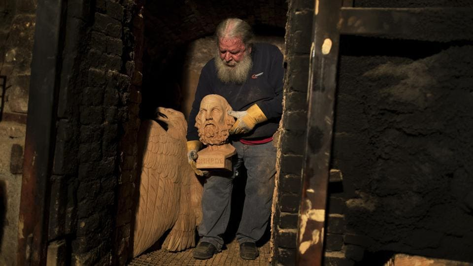 Sculptor and ceramicist Haralambos Goumas carries out of a furnace the bust of Homer, whom Greek tradition named as the author of the Iliad and Odysseyat his workshop, in the Egaleo suburb of Athens. Goumas, 67, is a man who fashions gods out of clay — a reversal of most ancient creation myths in which the gods make man. (Petros Giannakouris / AP)
