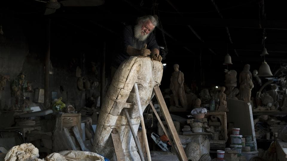 "Goumas works on a huge terracotta eagle in a mould at his workshop. ""I guess that in my lifetime I have made many more statues than those in China's Terracotta Army,"" Goumas told the Associated Press. (Petros Giannakouris / AP)"