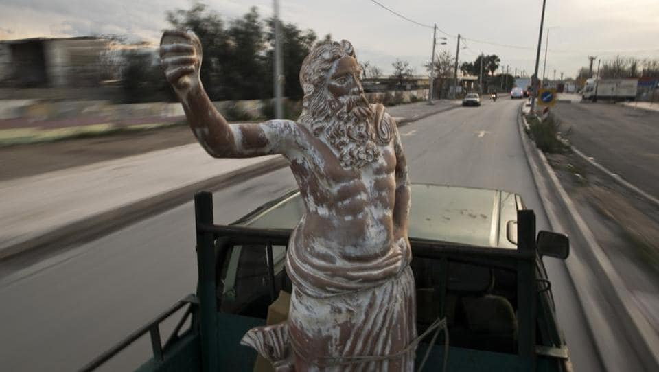 "A pickup truck drives on a street in Athens carrying one of Haralambos Goumas' creations --a terracotta statue of Zeus, chief among the ancient Greek pantheon. ""I have made so many gods that I believe one or other will help me. (Otherwise,) what did I make them all for?"" (Petros Giannakouris / AP)"