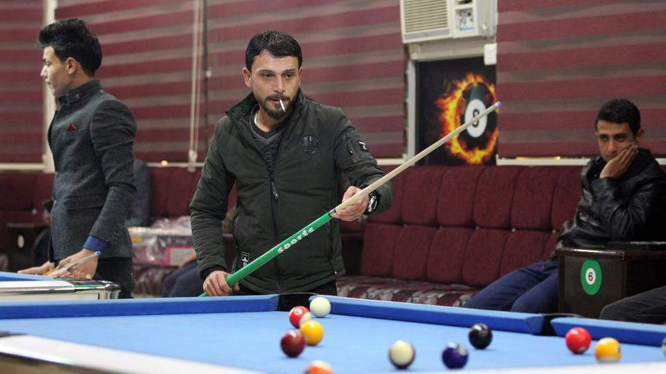 Iraqis play pool at a coffee shop on the eastern bank of the Iraqi city of Mosul on January 9, 2018, six months after chasing out the jihadists whoo took control of the city in 2014.
