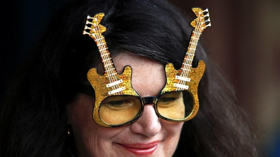 "An Elvis Presley fan wears glasses shaped in the form of guitars as she prepares to board the Elvis Express train. The focus this year is on celebrating 50 years since Presley's 1968 ""comeback special,"" an intimate and unplugged show credited with reviving his then-flagging recording career. (Daniel Munoz / REUTERS)"