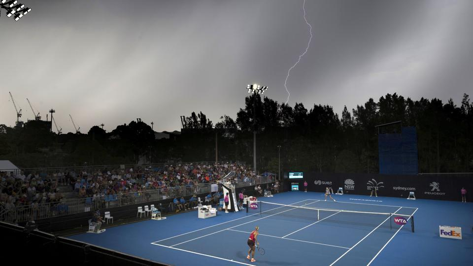 Lightning is seen in the sky above the court where Germany's Angelique Kerber plays her first-round match against Czech Republic's Lucie Safarova during the Sydney International on January 8, 2018. (AAP / Craig Golding via REUTERS)